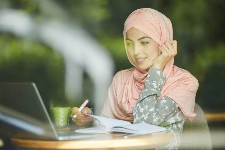 Woman in hijab watching webinar
