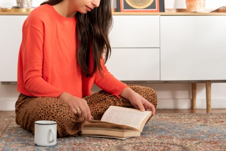 Young woman sitting on carpet and reading book at home