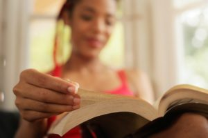 African American Woman Reading Book At Home Focus On Hand