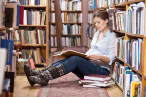 Young pregnant woman reading book