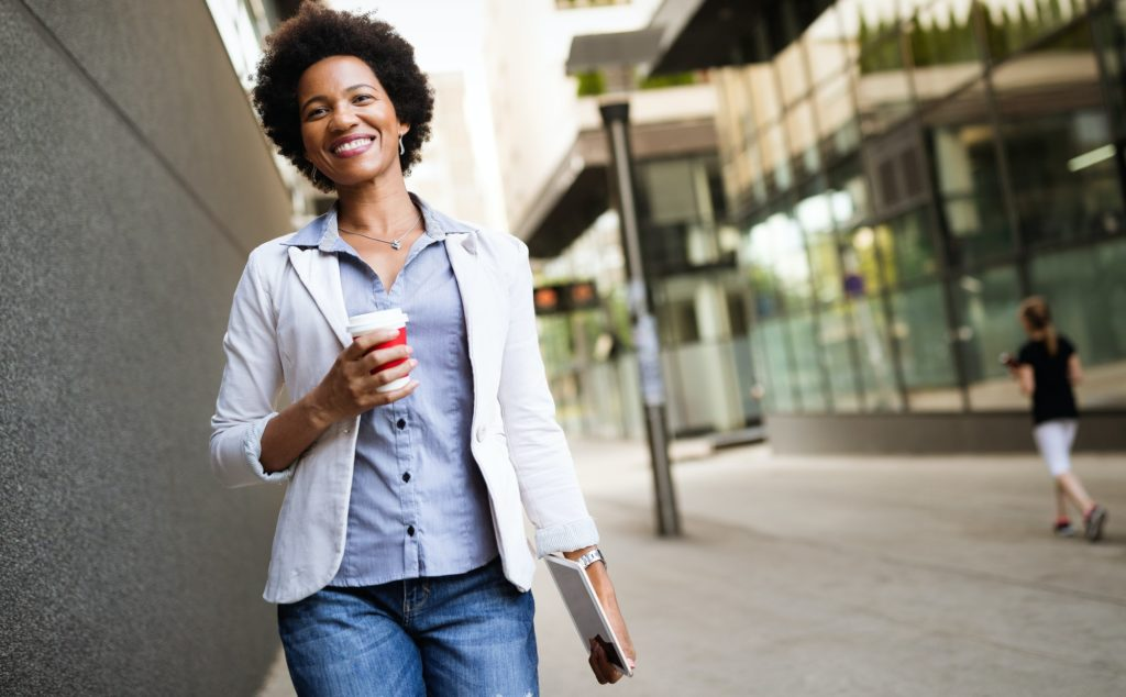 Smiling happy business woman, lawyer walking with coffee in city