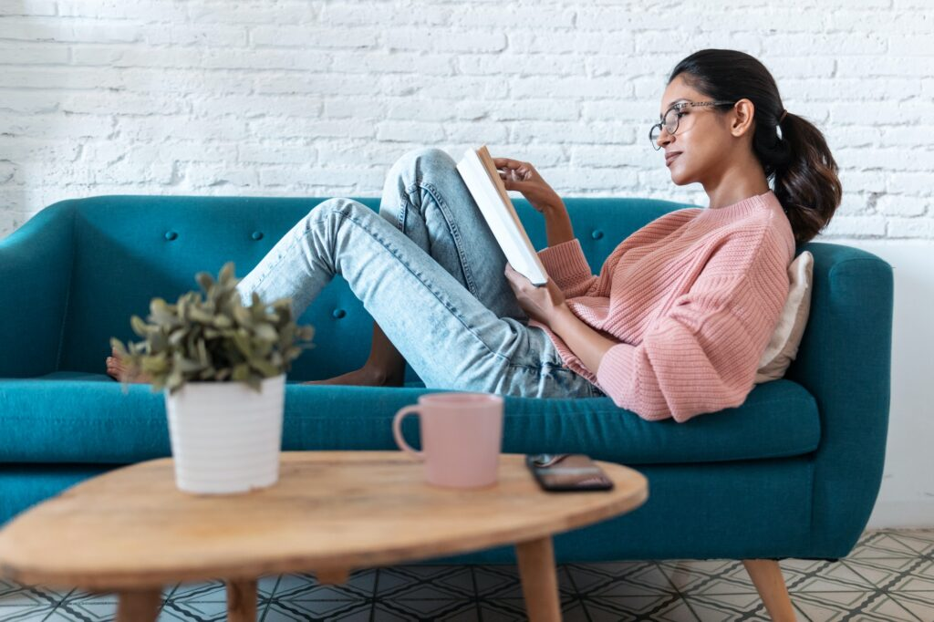 Pretty young woman reading a book while sitting on sofa at home.