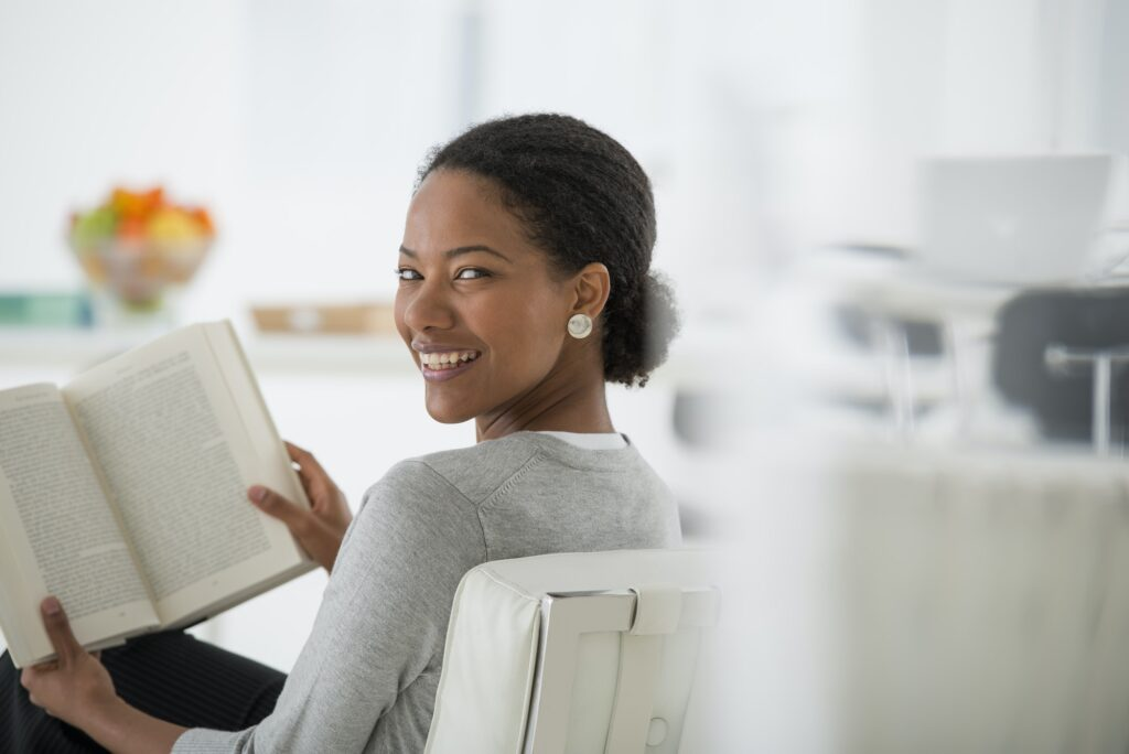 Business woman sitting and reading a book. Looking over her shoulder and smiling.